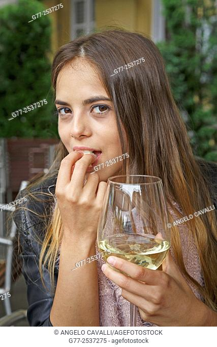 Young caucasian woman eating a piece of cheese and holding a glass of white wine