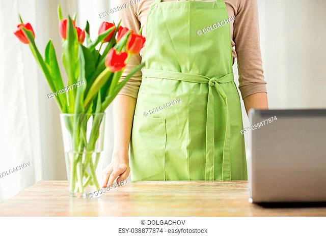 people, gardening, technology and profession concept - close up of woman with cut tulip flowers in vase and laptop computer at home