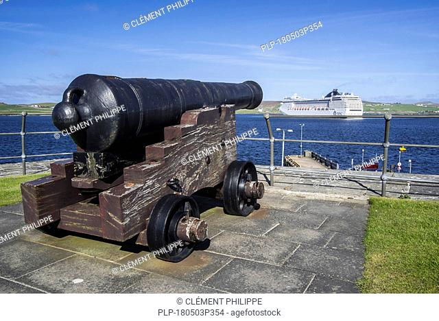 Cannon at 17th century Fort Charlotte in the centre of Lerwick and cruise ship in the Bressay Sound, Shetland Islands, Scotland, UK