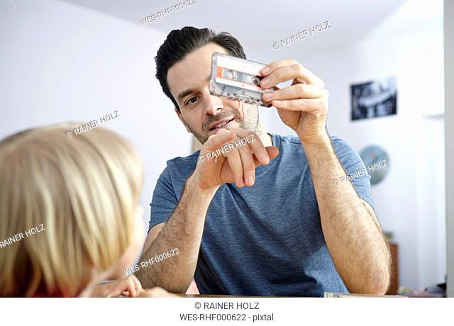 Man looking at old music cassette, showing tape to daughter
