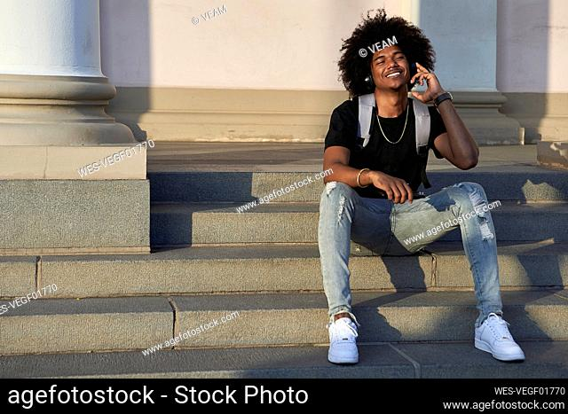 Young smiling man listening to music and sitting on steps