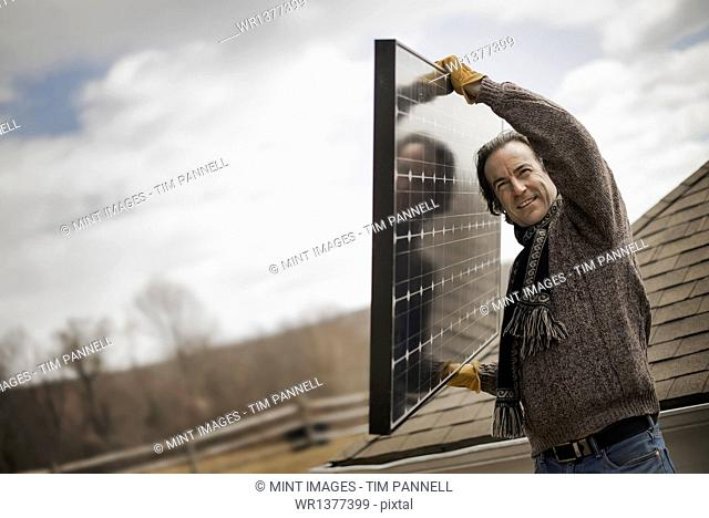 A man carrying a large solar panel across a farmyard