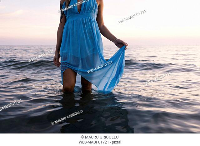 Young tattooed woman wearing blue dress standing in the sea by sunset, partial view