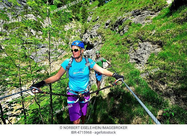 Two climbers on suspension bridge, via ferrata Hausbachfall, Reit im Winkl, Chiemgau, Bavaria, Germany
