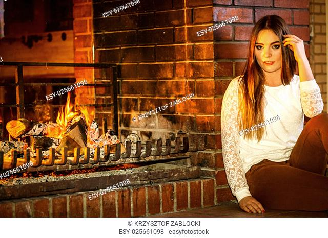 pensive woman relaxing at fireplace. winter home