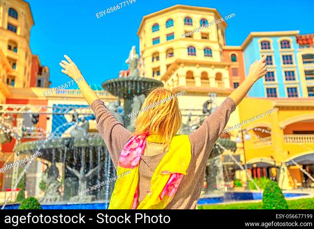 Carefree blonde woman enjoys water fountains in Central Medina, an exclusive residential area in The Pearl Qatar, icon of Doha, Persian Gulf, Middle East