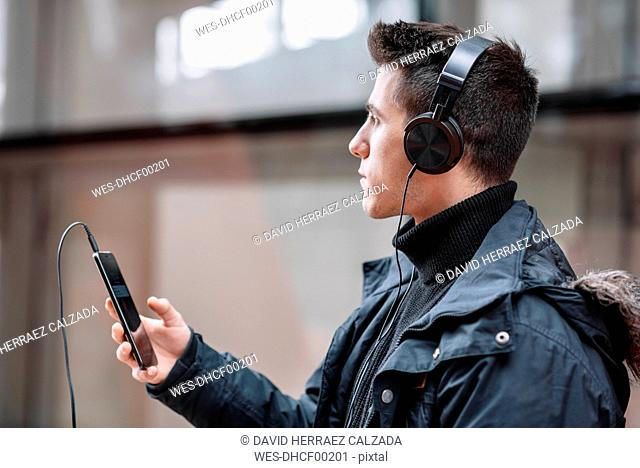 Young man with smartphone and headphones listening to music