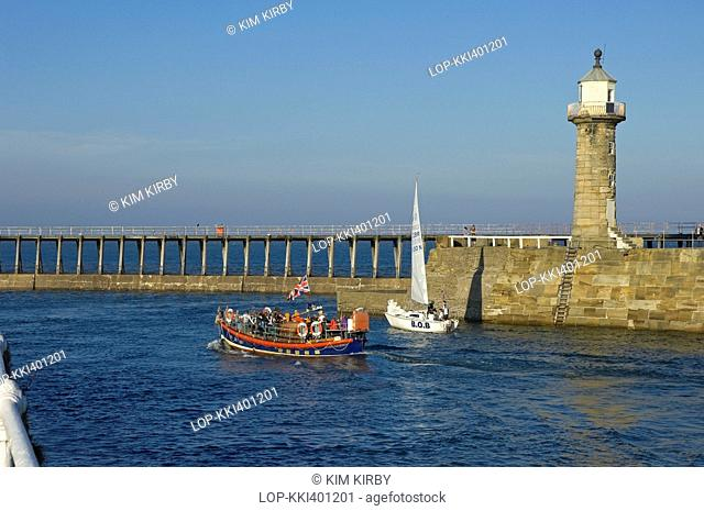 England, North Yorkshire, Whitby. Tourists enjoying a pleasure trip onboard Whitby's Old Lifeboat as it makes it's way out to sea between the the East and West...
