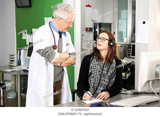 Doctor in a white coat with stethoscope, discussing the planning and appointment list with a nurse and receptionist in a medical emergency call center in a...