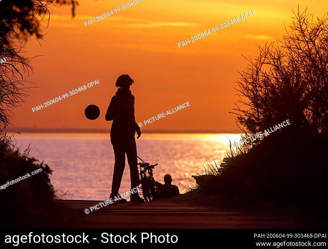 02 June 2020, Mecklenburg-Western Pomerania, Timmendorf (poel): A young man plays with a ball after sunset on a beach access on the island of Poel