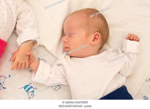 Newborn twins sleeping hand in hand