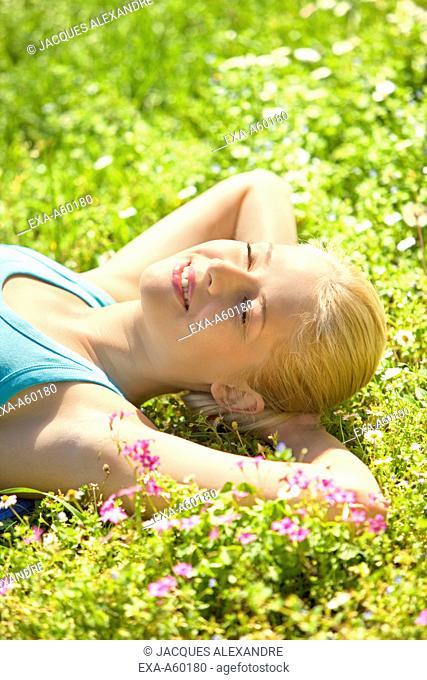 Young woman with eyes closed resting on the flowers at park