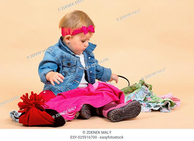 portrait of young cute baby on beige background checking winter clothing