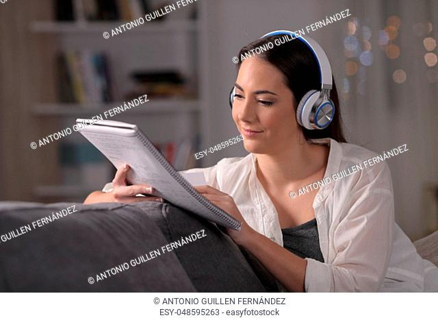 Serious student wearing headphones reading notes on a couch at home in the night