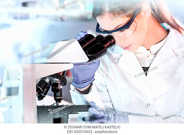 Life scientists researching in laboratory. Attractive female young scientist microscoping in their working environment. Healthcare and biotechnology