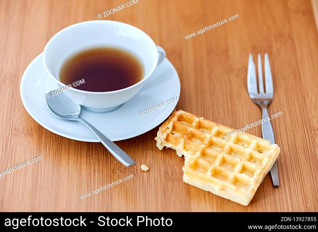 Wooden table with white cup with saucer and spoon as well as lying next to bitten waffle and cake fork with shallow depth of field