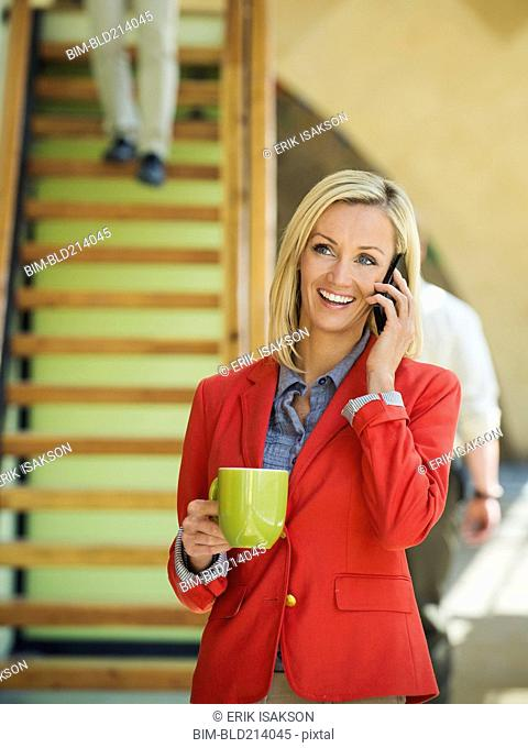 Businesswoman talking on cell phone near staircase