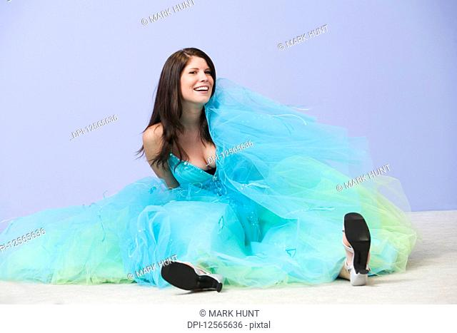 View of a young woman sitting on the floor in prom dress