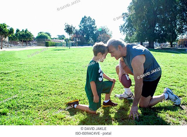 Boy and grandfather head to head, man holding football