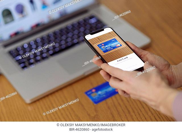 Woman with iPhone X smartphone in her hand scanning a credit card with Apple Pay, Apple Wallet electronic payment app