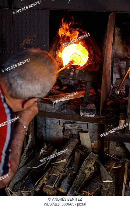 Man blowing glass with a tube using a furnace in a glass factory in Mallorca