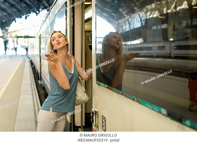 Young woman entering a train at the train station blowing a kiss