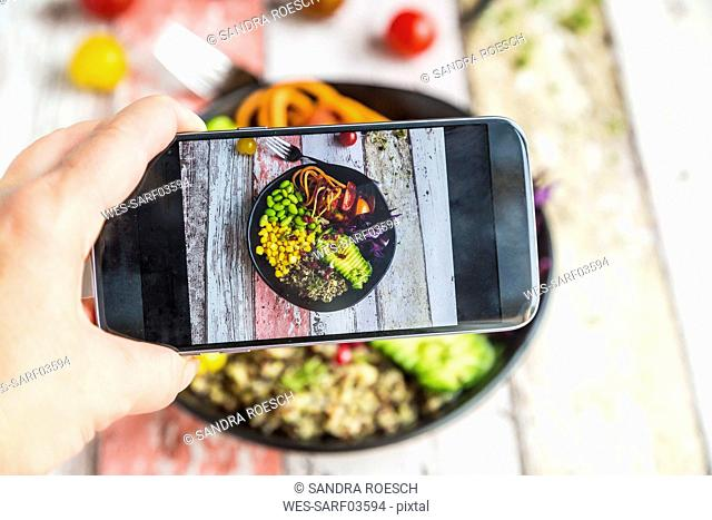 Girl taking photo of vegan Lunch bowl with cell phone, close-up