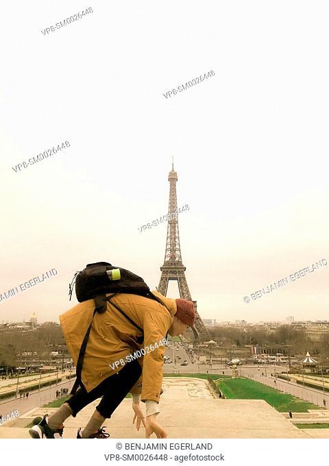 young Millennial tourist climbing on platform at Trocadéro next to touristic sight Eiffel Tower, exploring city Paris, France