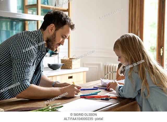 Father and daughter drawing at home
