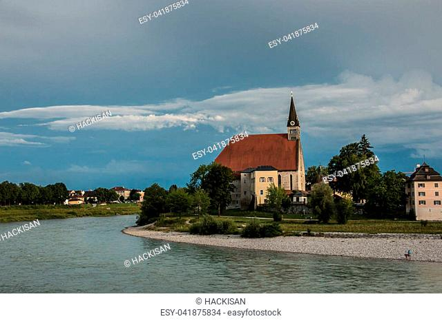 Old church with green trees and green grass near by the river