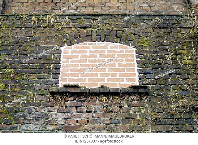 Small window in an old brick wall, freshly sealed with bricks as protection against vandalism, Essen, Ruhr Area, North Rhine-Westphalia, Germany, Europe