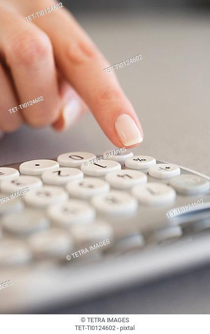 Close up of woman using calculator