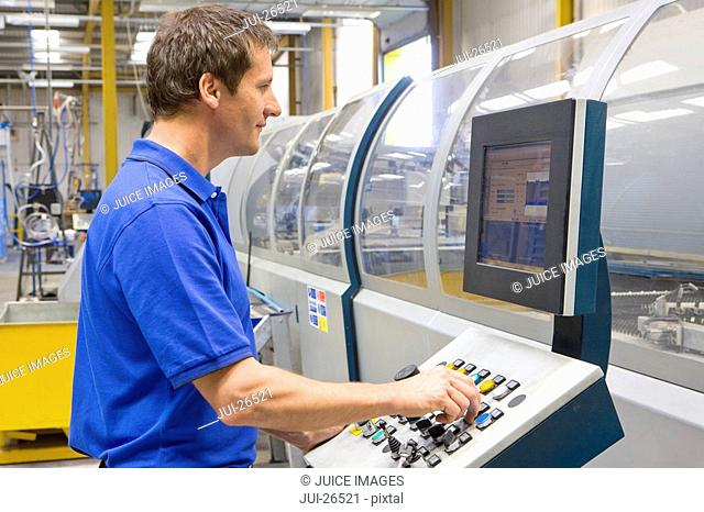 Worker adjusting buttons on factory control panel