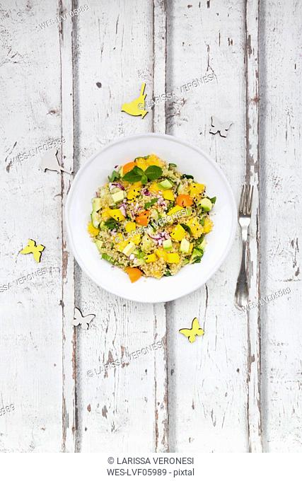 Plate of quinoa salad with mango, avocado, tomatoes, cucumber, herbs and black sesame
