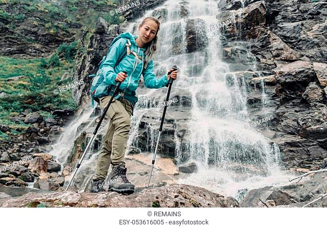 Smiling backpacker young woman with trekking poles standing near the waterfall