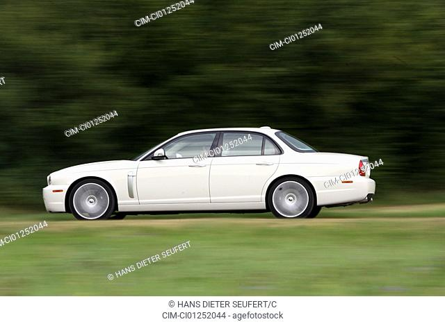 Jaguar XJR model year 2007, white, driving, side view, country road