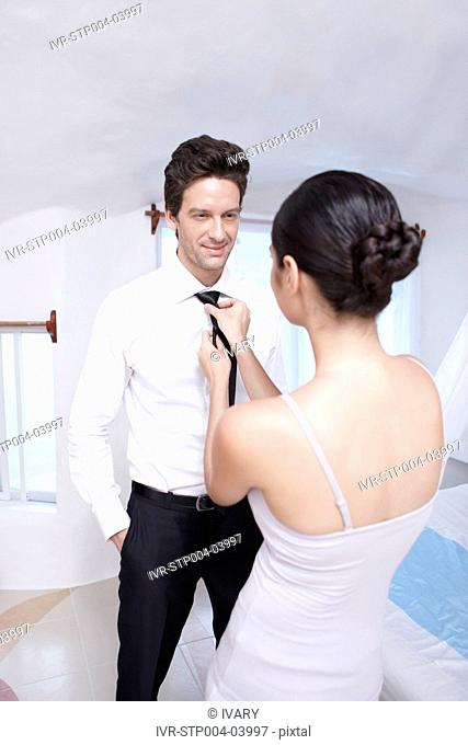A young woman helping a man with his tie