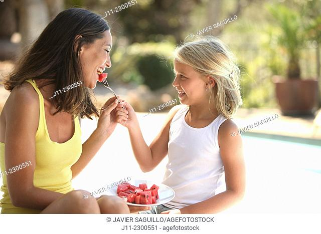 Mother and daughter, eating watermelon