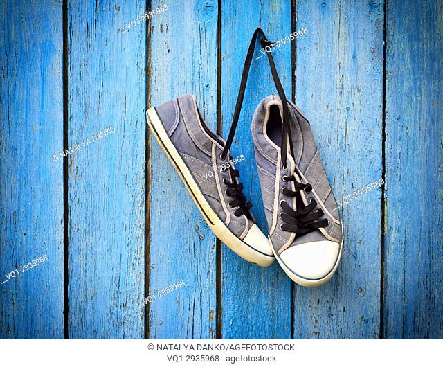 old men's shabby textile sneakers hang on a nail on a blue wooden wall