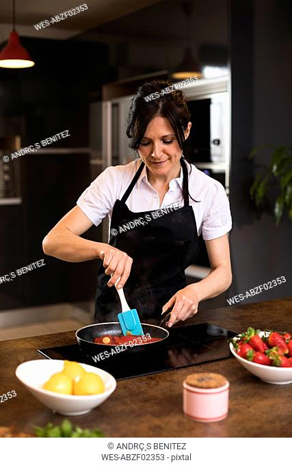 Woman cooking in kitchen using a pan