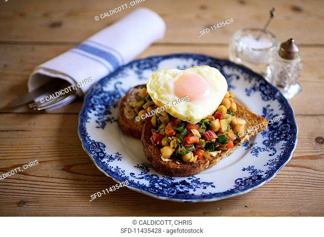 A slice of toast topped with tomatoes, chard, chickpeas and a heart-shaped fried egg