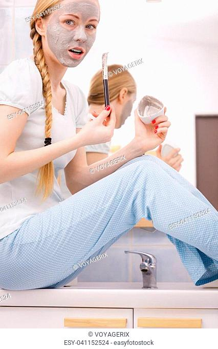 Skincare. Young woman wearing nightwear sitting on sink in bathroom, applying with brush gray clay mud mask to her face. Teen girl taking care of skin