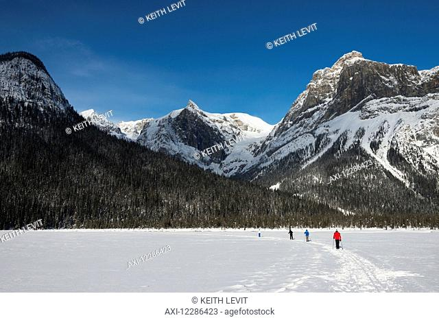 Walking and skiing in the snow on frozen Lake Louise; Lake Louise, Alberta, Canada