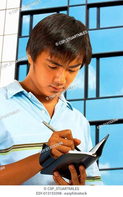 Man Writing In His Organizer