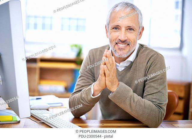 A portrait of a happy businessman sitting at his desk at work