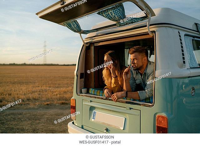 Couple brushing teeth in camper van in rural landscape