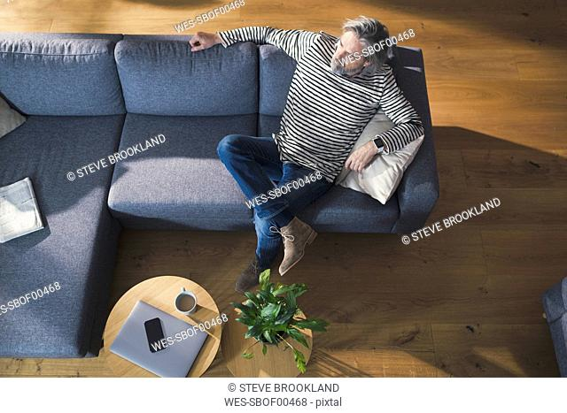 Senior man sitting on couch, relaxing and thinking