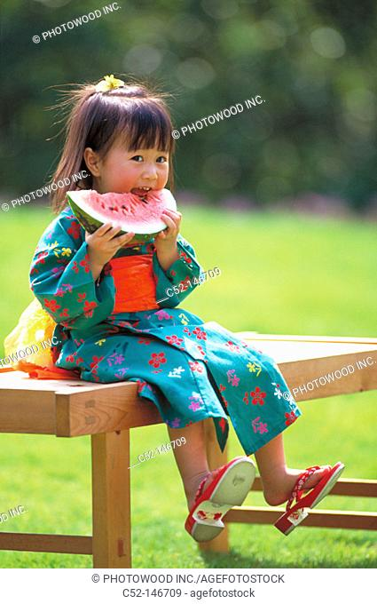 Asian girl eating water melon