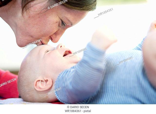 Mother kissing baby boy, Munich, Bavaria, Germany