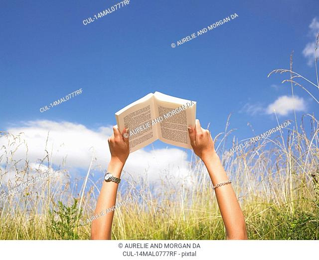 woman reading in field of high grasses